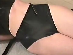 buxom ginger in latex bound with leather straps